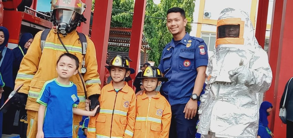berpose menggunakan PMK orange, Baju dinas tahan api.