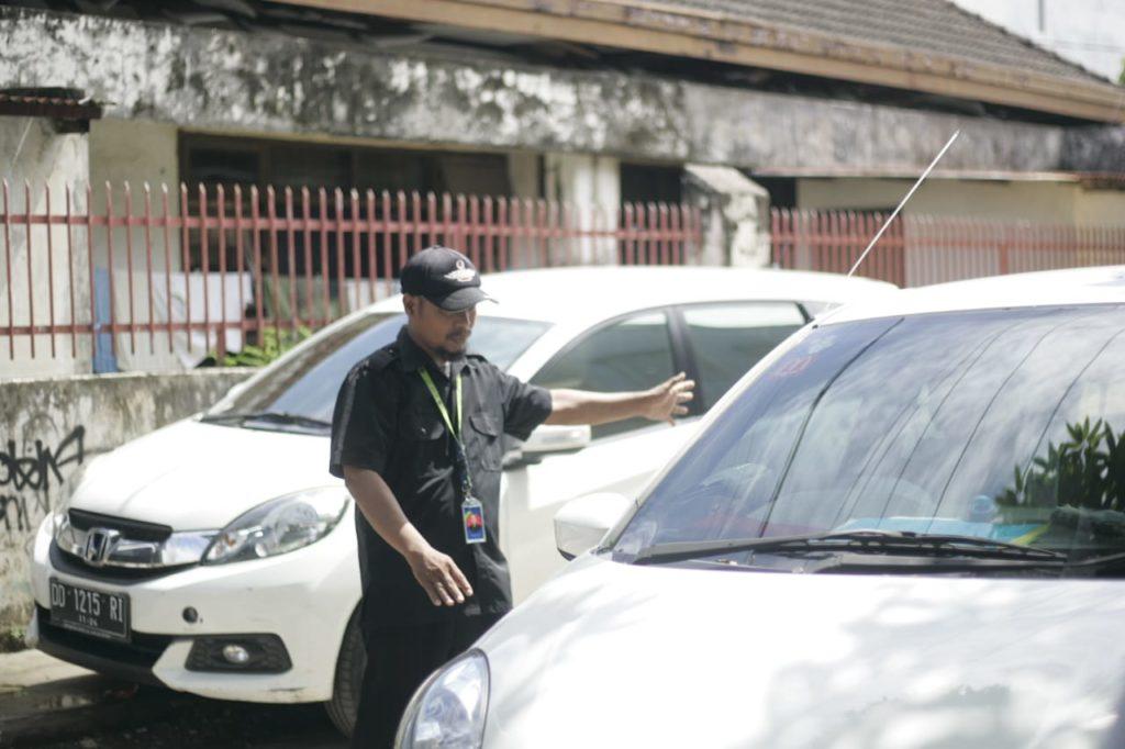 Security membantu calon pembeli memarkirkan kendaraan