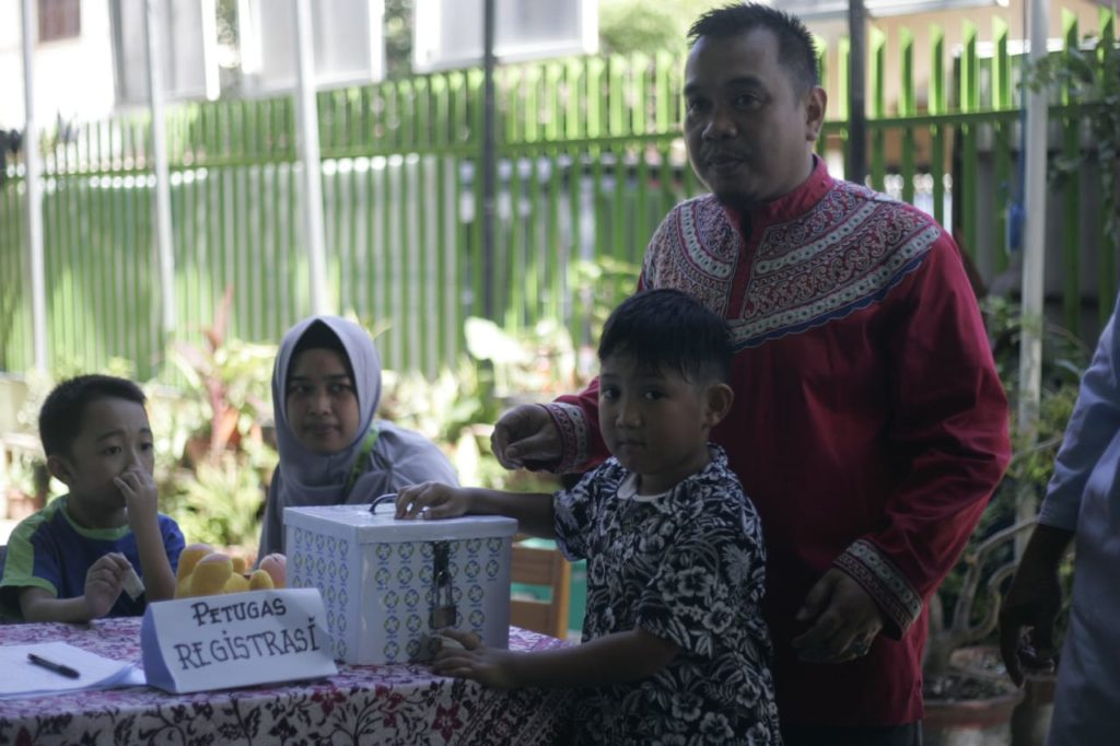 Seorang siswa SD memasukkan sumbangan ke dalam kotak infak JARI