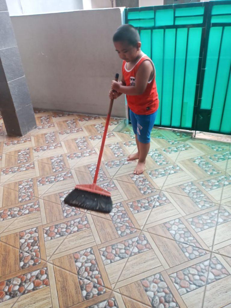 Ananda kelas KB membantu bunda menyapu lantai