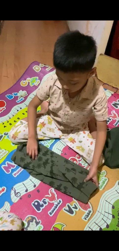 Ananda kelas A2 membantu bunda melipat pakaian