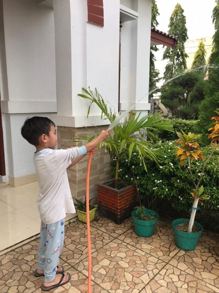 Ananda kelas B4 membantu bunda menyiram tanaman