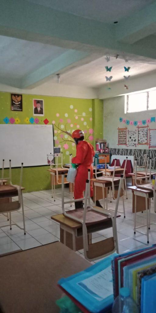 Petugas menyemprot desinfektan pada kursi dan meja di ruangan kelas SD